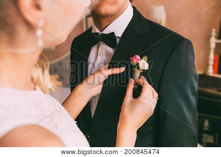 Wedding . Close-up bride's hands pinning boutonniere to groom's tuxedo. Warm tones. Wedding preparation
