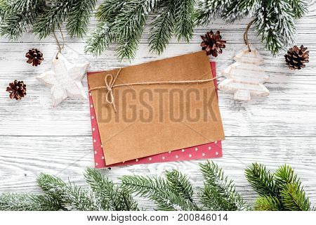 Mockup for new year 2018. Sheet of paper, greeting card near spruce branches, pine cone on light wooden background top view.