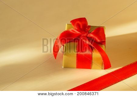 Holidays present concept. Small golden box with gift tied decorative bow and red ribbon