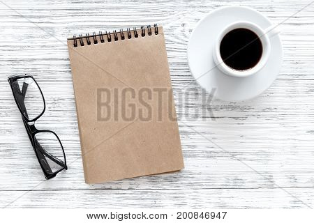 Mockup for goals list for 2018. Notebook, glasses and cup of coffee on grey wooden background top view.