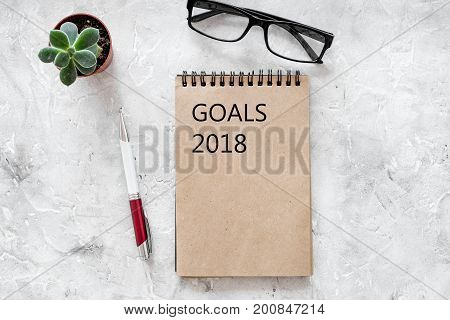 Words Goals for 2018 writting in notebook near glasses on grey stone background top view mockup.