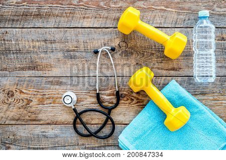 Sport and health. Fitness. Dumbbells and stethoscope on wooden background top view.