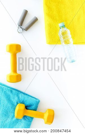 Equipment for fitness. Dumbbells and expander on white background top view.