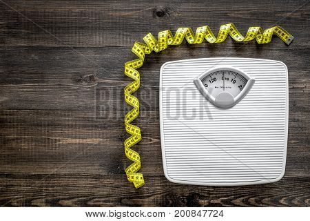 Bathroom scale and measuring tape on wooden background top view.