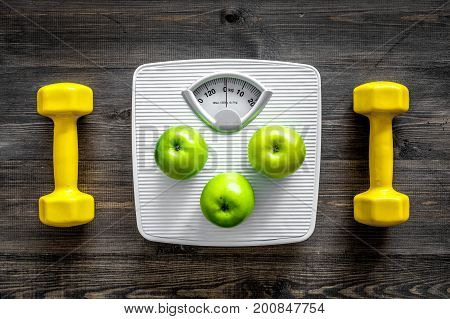 Sport and diet for losing weight. Bathroom scale, apple and dumbbell on wooden background top view.