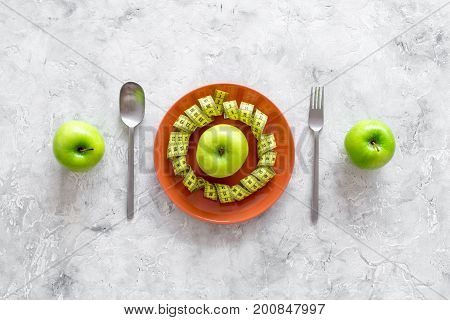 Slimming diet. Apple at plate and measuring tape on grey stone background top view.