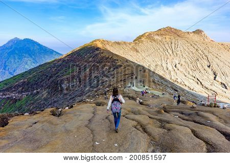Hikers tourist trekking along dusty section of Ijen trail. Kawah Ijen is an active volcano located in Banyuwangi is famous for sulphur mining and its blue fire.