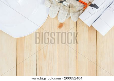 Safety equipment and tool kit on wooden background with copy space. personal safety accessories on surface. Items include a hard hat with safety goggles wrenches