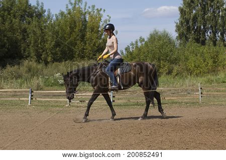Women is horse riding - red hair girl in summer meadow, telephoto