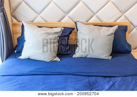 Comfortable bedroom with white bed sheet blue pillows and turn light on bed