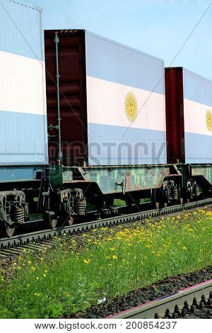 Train Freight transportation. Cargo transit. Summer Day. Container textured by flag of the Argentina