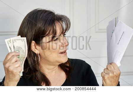 Upset Middle Aged Woman Holding Bills Due And Currency