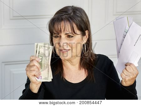 Worried Middle Aged Woman Holding Bills Due And Currency