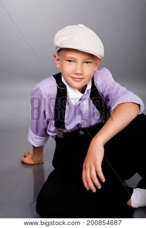 Old Fashioned Boy Sitting On Gray Background
