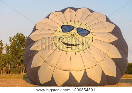 A hot air balloon with a smiling sun face wearing blue sunglasses on the top. The balloon is being inflated at sunrise.
