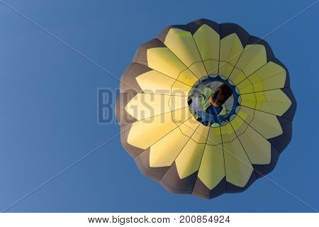 A yellow and black hot air balloon in flight. The flame is seen above the wicker basket carrying passengers. The deep blue sky is cloudless. Image has copy space.