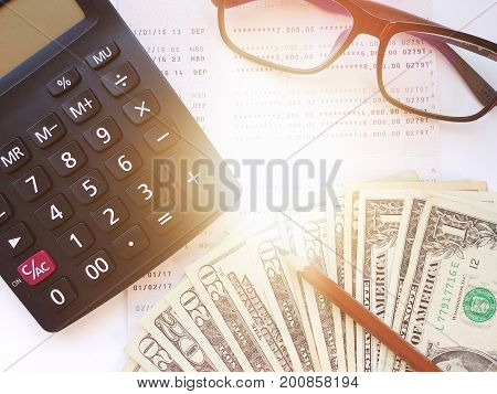 Business, finance, savings, banking or loan concept : Pencil, calculator, money, eyeglasses and savings account passbook or financial statement on white background