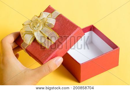 Open red gift box in hand on yellow color background for giving in holidays
