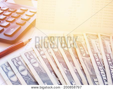 Business, finance, savings or loan concept : Money, calculator and pencil on saving account passbook or financial statement