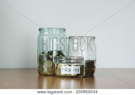 Coins In Glass Jars For Different Needs, Money Boxes. Distribution Of Cash Savings Concept. Car Stic