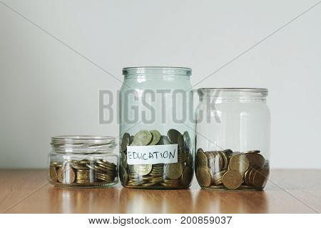 Coins In Glass Jars For Different Needs, Money Boxes. Distribution Of Cash Savings Concept. Educatio