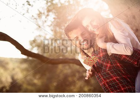 Portrait of smiling handsome man giving piggy back to his girlfriend in the nature.