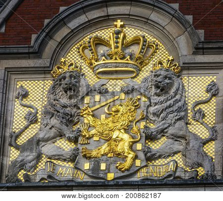 AMSTERDAM, NETHERLANDS - MARCH 30, 2017   Netherlands Coat of Arms Amsterdam Holland Netherlands. On Building Facing the Canal. Also symbol of Dutch Monarchy. Combines Lion of Dutch Republic with Nassau/Orange symbol. Je Maintiendrai