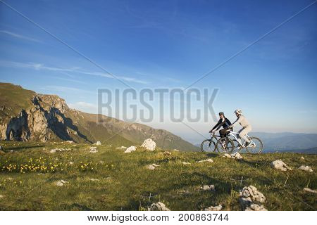 Happy mountainbike couple outdoors have fun together on a summer afternoon.