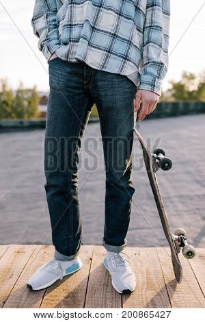 Skateboarder with skateboard. Street subculture, modern youth, extreme for young people, unrecognizable male