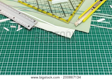 Paper Sheets With Metal Ruler And Utility Knife On Green Cutting Mat
