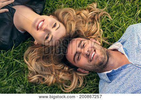 Happy Smiling Couple Relaxing on Green Grass.Park.Young Couple Lying on Grass Outdoor. Elegantly dressed.