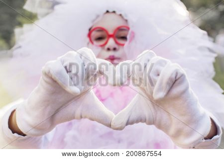 Young woman in a carnival costume meringue makes a heart from her fingers. The character sends a kiss and love. Beautiful asian girl showing her love with hand sign in the park