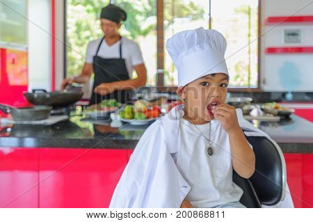 Cute Little Thai Boy In Chef's Hat And Tunic Sitting On A High Chair In A Modern Style Home Kitchen.