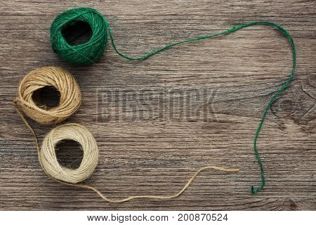 Balls of yarn in green and beige color on a wooden surface. Linen thread in a tangle. The view from the top.