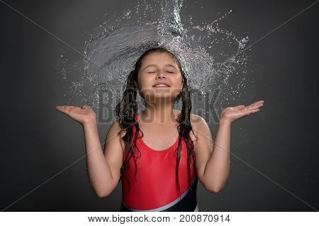 Smiling teenaged girl in swimsuit catching water stream and splashes falling on her from top