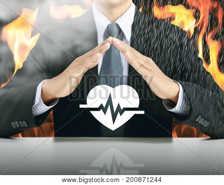 businessman and heartbeat with fire background, insurance concept