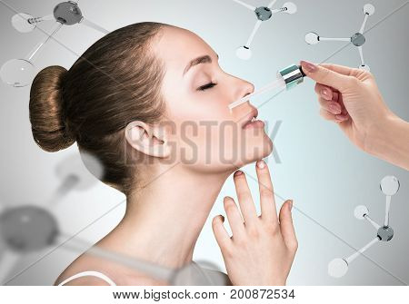 Young woman with cosmetics oil on face among the molecules. Over gray background. Skin therapy concept.