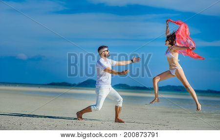 An elegant couple having fun at a desert beach, jumping and fluttering like butterfly