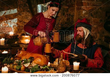 Medieval people eat and drink in castle tavern.