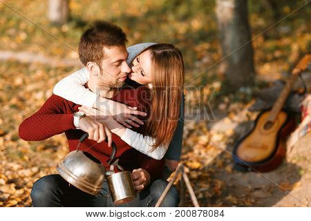 autumn camping. happy couple hugging and making tea or coffee. warm drinks. metal teapot and cups