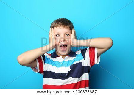 Portrait of emotional boy on blue background
