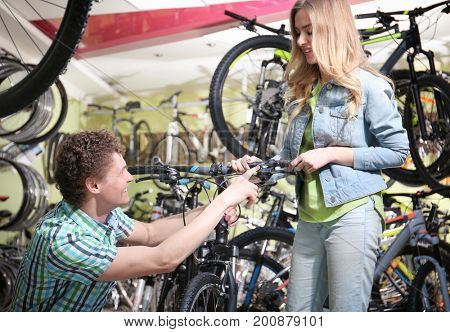 Young couple choosing bicycle in shop