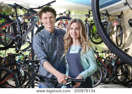 Young man and pretty seller in bicycle shop