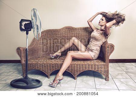 Woman Enjoying Breeze With Electric Fan