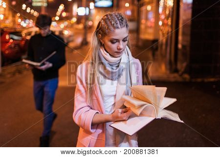 Bookworm on night street. Interesting reading. Student studying outside, search for information in textbook