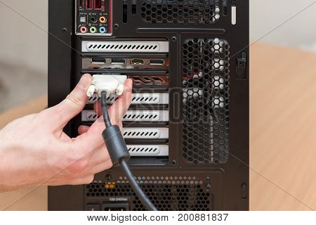 Man hand connecting the DVI cable for monitor to computer PC