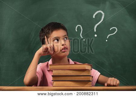 Boy with doubts and thoughts in class. Portrait of male child thinking against question marks on blackboard