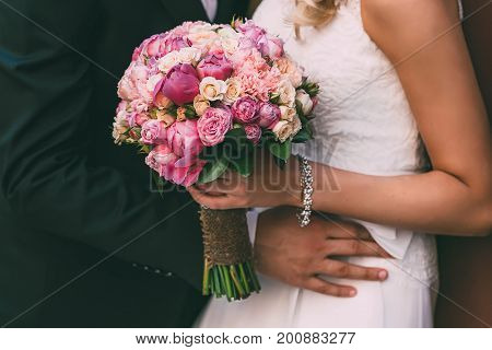 The Beautiful bride holds a wedding bouquet with pink roses and peonies. Groom embrace woman by the waist. Outdoors