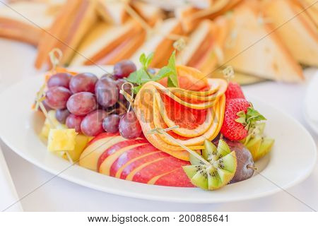 White fruits plate with strawberry grape-fruit grapes orange herbs and cheese. Close up image with selective focus