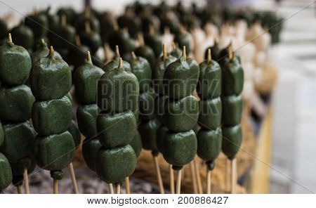 Street food on sale outside a temple in Kyoto, Japan - matcha tea flavour lollies on sticks